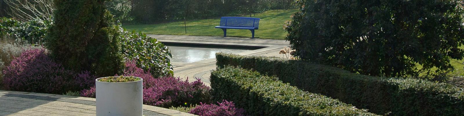 Een doorkijkje naar een blauw bankje bij de vijver.